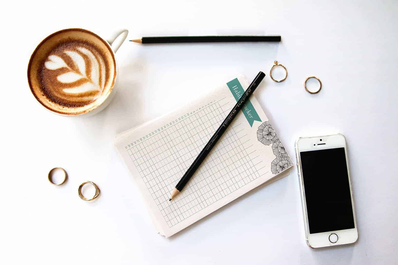 Habit Tracker on a Table with a Coffee and Phone