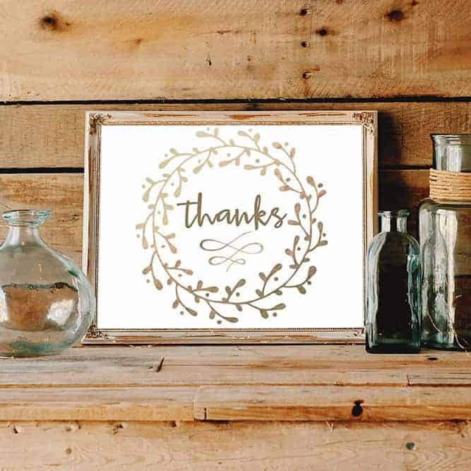"free art print that says ""thanks"" with a wreath around it, in a wood frame on a wooden ledge with glass bottles"